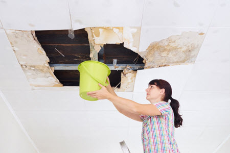 woman with bucket for leaky ceiling